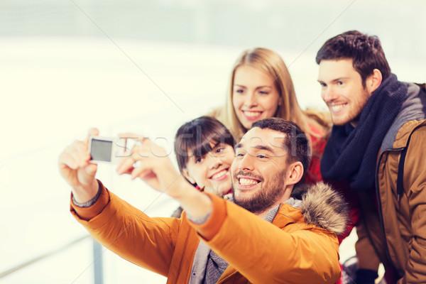 happy friends with camera on skating rink Stock photo © dolgachov
