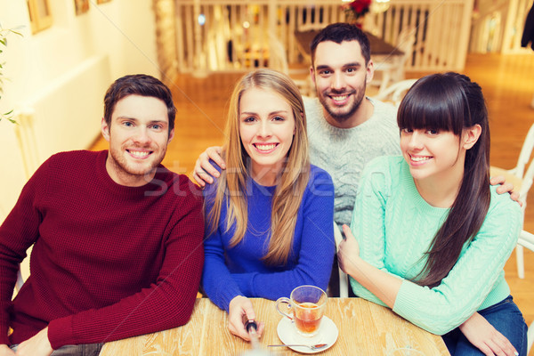 group of friends taking picture with selfie stick Stock photo © dolgachov