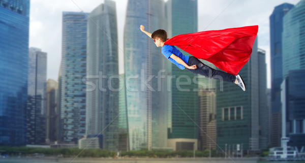 boy in red superhero cape and mask flying on air Stock photo © dolgachov