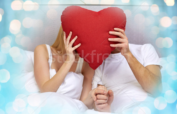 happy couple in bed with red heart shape pillow Stock photo © dolgachov