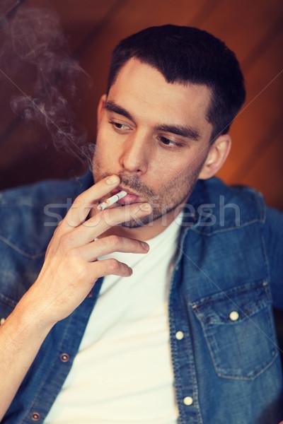 young man smoking cigarette at bar Stock photo © dolgachov