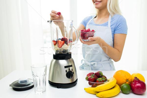 close up of woman with blender making fruit shake Stock photo © dolgachov