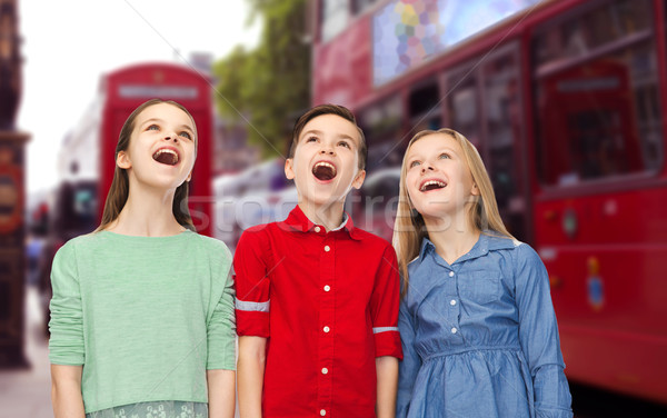 amazed boy and girls looking up over london city Stock photo © dolgachov