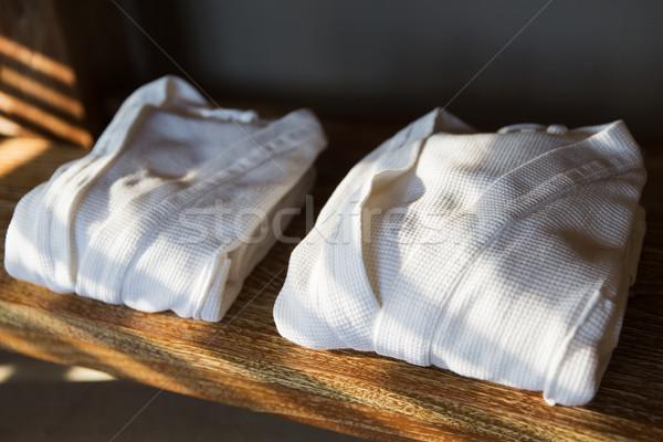 close up of two white bathrobes on wooden shelf Stock photo © dolgachov
