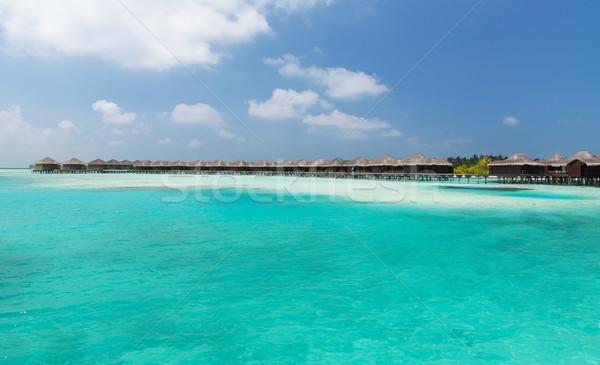 bungalow huts in sea water on exotic resort beach Stock photo © dolgachov