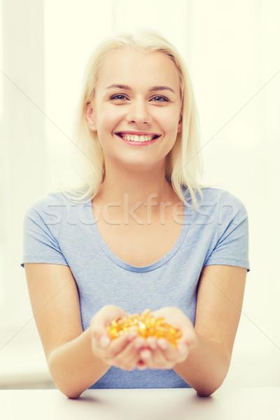 Boldog nő tart halolaj kapszulák otthon Stock fotó © dolgachov