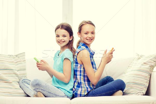 Felice ragazze smartphone seduta divano persone Foto d'archivio © dolgachov