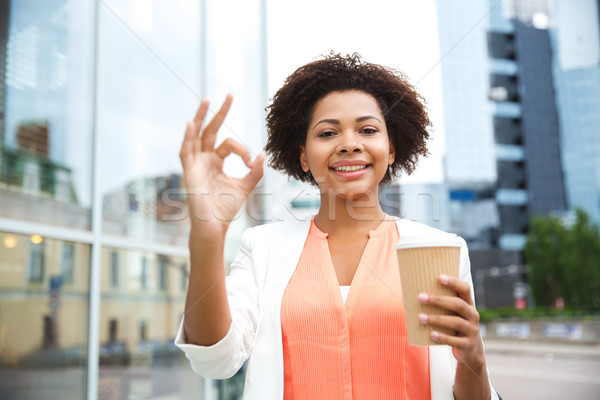 happy woman with coffee showing ok up in city Stock photo © dolgachov