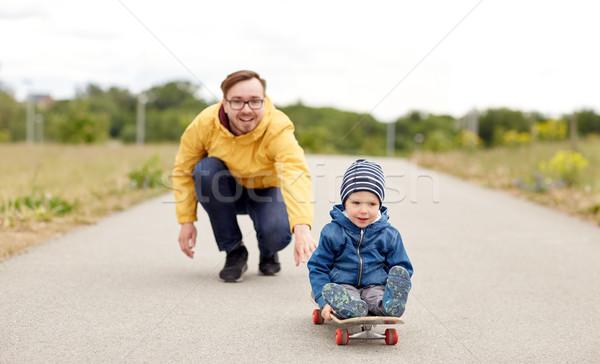 Boldog apa kicsi fiú lovaglás gördeszka Stock fotó © dolgachov
