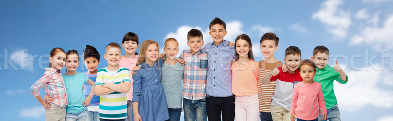 group of happy children hugging over blue sky Stock photo © dolgachov