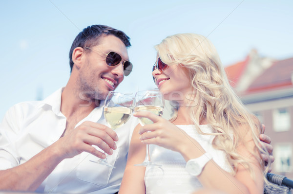 smiling couple in sunglasses drinking wine in cafe Stock photo © dolgachov
