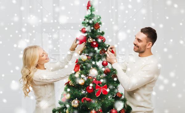 Stock photo: happy couple decorating christmas tree at home