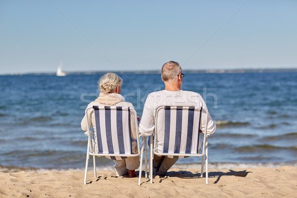 senior couple sitting on chairs at summer beach Stock photo © dolgachov