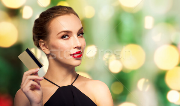 beautiful woman with credit card over black Stock photo © dolgachov