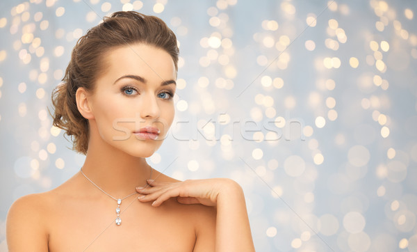 Stock photo: beautiful woman wearing shiny diamond pendant