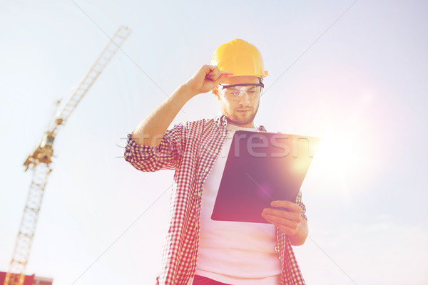 builder in hardhat with clipboard outdoors Stock photo © dolgachov