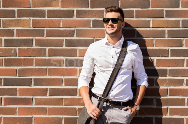 young man in sunglasses with bag over brickwall Stock photo © dolgachov