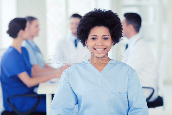 happy doctor over group of medics at hospital Stock photo © dolgachov