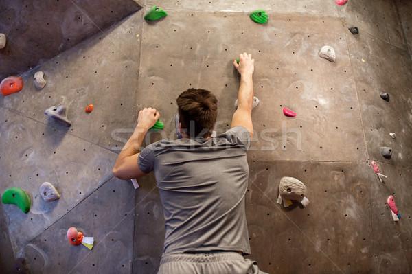 young man exercising at indoor climbing gym wall Stock photo © dolgachov