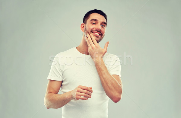 happy young man applying cream or lotion to face Stock photo © dolgachov
