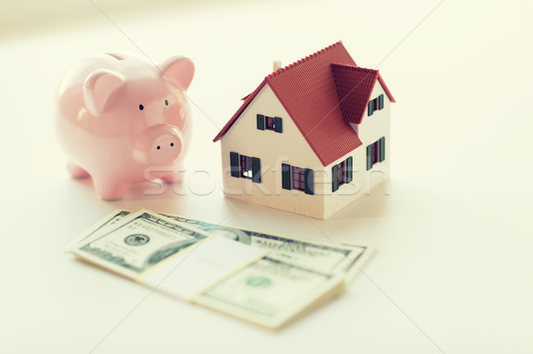 close up of house model, piggy bank and money Stock photo © dolgachov