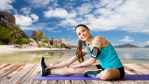 woman with smartphone stretching leg on mat Stock photo © dolgachov