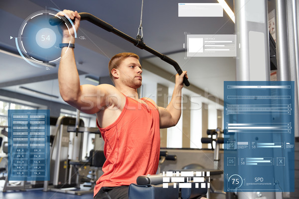 man flexing muscles on cable machine gym Stock photo © dolgachov