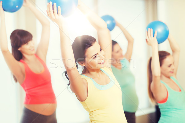 Stock photo: happy pregnant women exercising with ball in gym