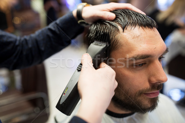 man and barber hands with trimmer cutting hair Stock photo © dolgachov