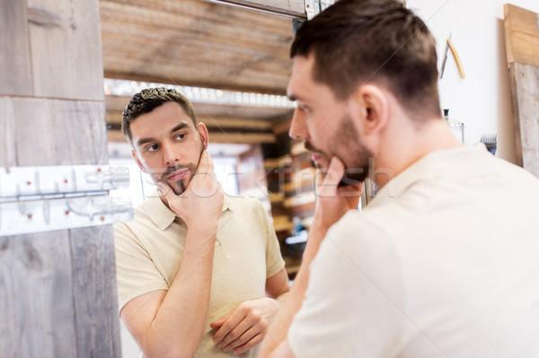 man looking at himself at barbershop mirror Stock photo © dolgachov