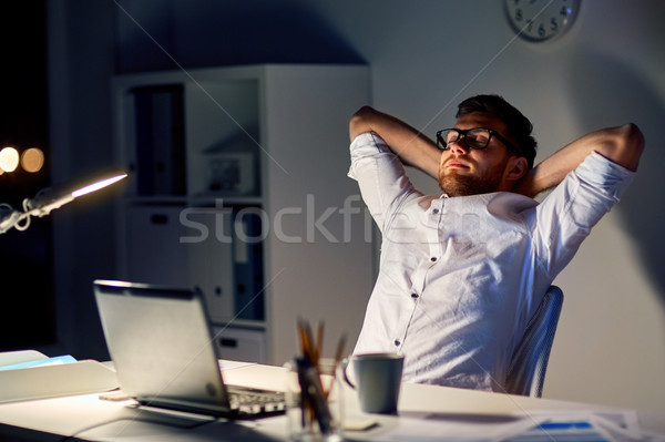 man with laptop stretching at night office Stock photo © dolgachov