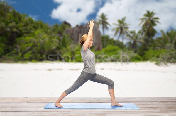 Szczęśliwy kobieta jogi wojownika stanowią plaży Zdjęcia stock © dolgachov