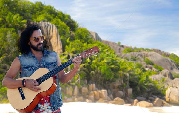 hippie man playing guitar over island beach Stock photo © dolgachov