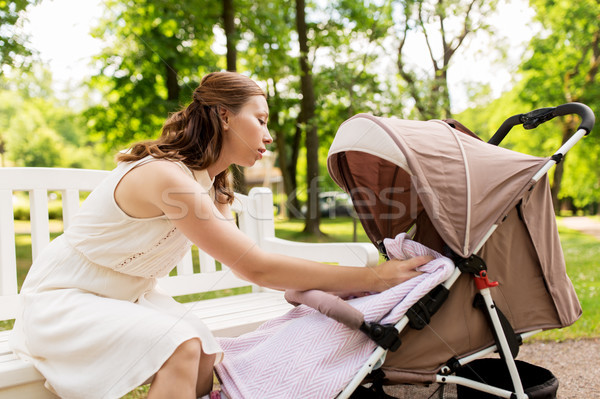 happy mother with child in stroller at summer park Stock photo © dolgachov