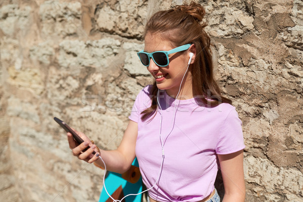 teen girl with longboard, smartphone and earphones Stock photo © dolgachov