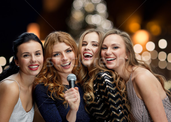 women with microphone singing karaoke at christmas Stock photo © dolgachov