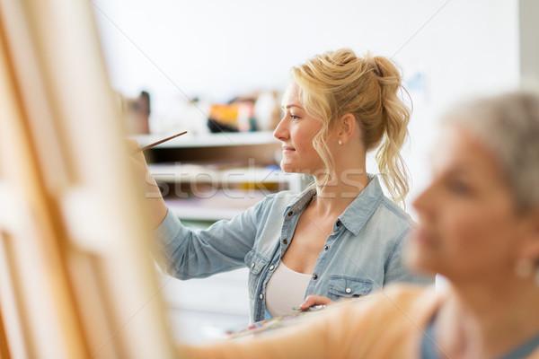woman artist with brush painting at art school Stock photo © dolgachov