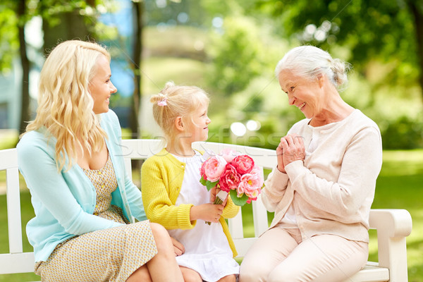Stock photo: happy family giving flowers to grandmother at park