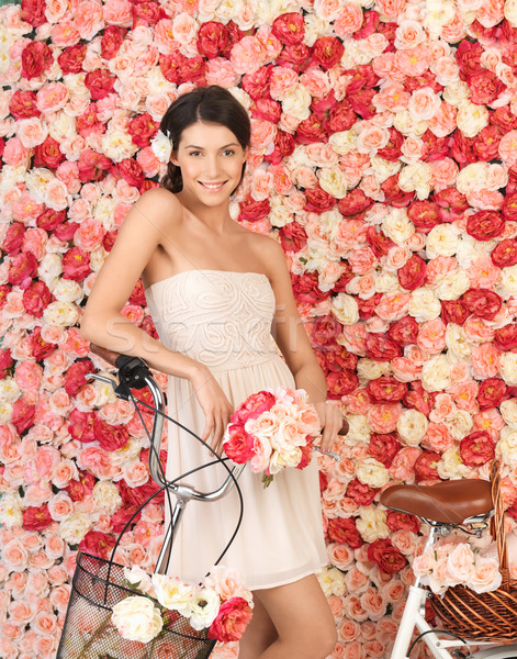 woman with bicycle and background full of roses Stock photo © dolgachov
