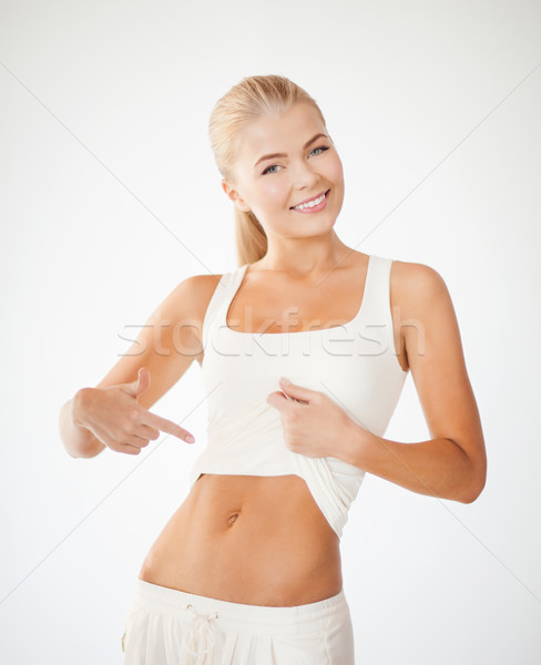 beautiful sporty woman pointing at abs Stock photo © dolgachov