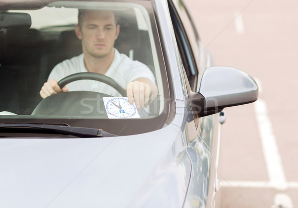 man placing parking clock on car dashboard Stock photo © dolgachov