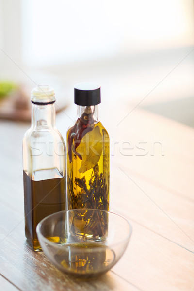 close up of two olive oil bottles and bowl of oil Stock photo © dolgachov