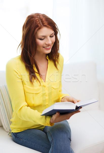 Mosolyog tinédzser olvas könyv ül kanapé Stock fotó © dolgachov