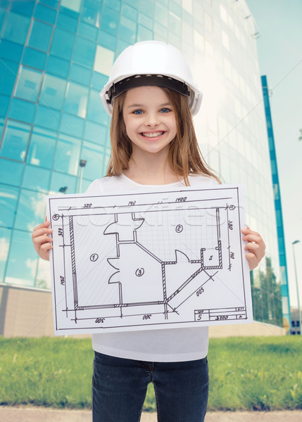 smiling little girl in helmet showing blueprint Stock photo © dolgachov