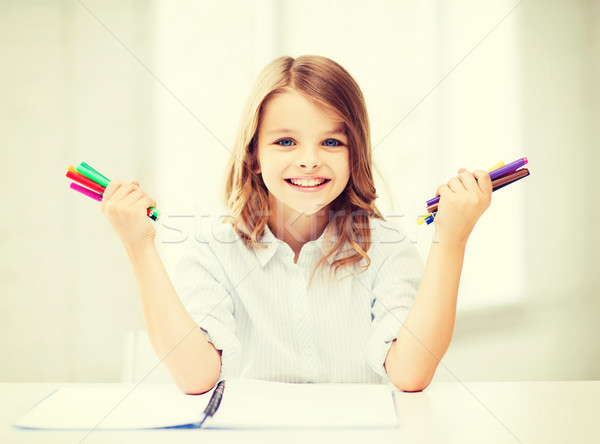 Stock photo: smiling girl showing colorful felt-tip pens