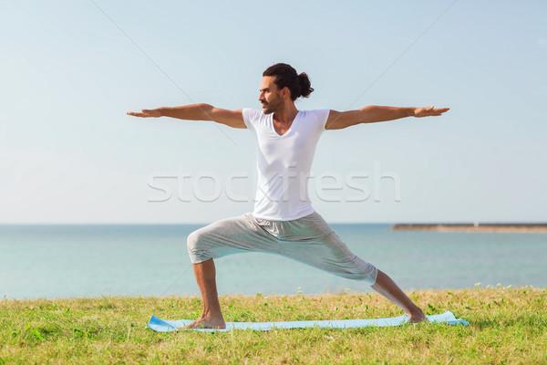 smiling man making yoga exercises outdoors Stock photo © dolgachov