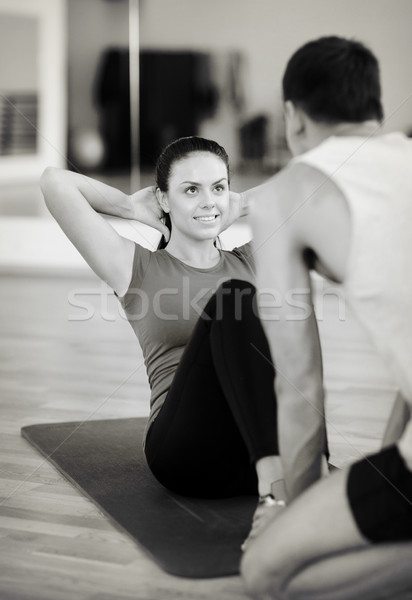 male trainer with woman doing sit ups in the gym Stock photo © dolgachov