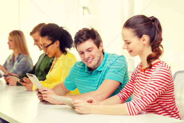 smiling students looking at tablet pc at school Stock photo © dolgachov