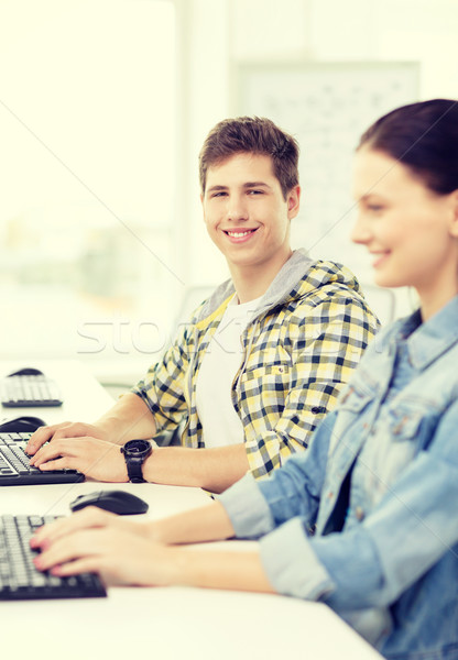smiling boy with girl in computer class at school Stock photo © dolgachov