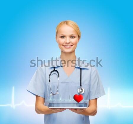 smiling doctor or nurse pointing to pills icon Stock photo © dolgachov